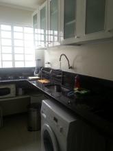 Cozinha funcional e bem equipada, com fogão ao lado da janela e máquina lava e seca