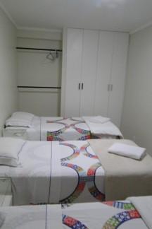 Quarto com armário e três camas de solteiro.