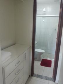 Antes de entrar no banheiro, você passa pelo closet com gaveteiro, maleiro e cabideira.