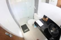 Banheiro com box blindex, finamente decorada com pastilhas, e bancada em granito.