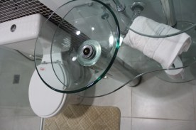 Banheiro todo moderninho com a cuba transparente