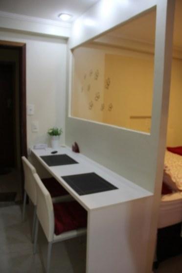 A mesa de estudo e jantar é dividida do quarto por uma parede com vidro: perfeito pra quem quer jantar assistino TV