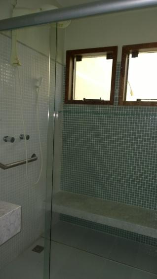 Banheiro com banco de mármore e barras: adaptado para a terceira idade.